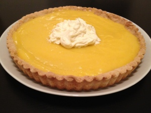 A homemade lemon curd tart with whipped cream topping